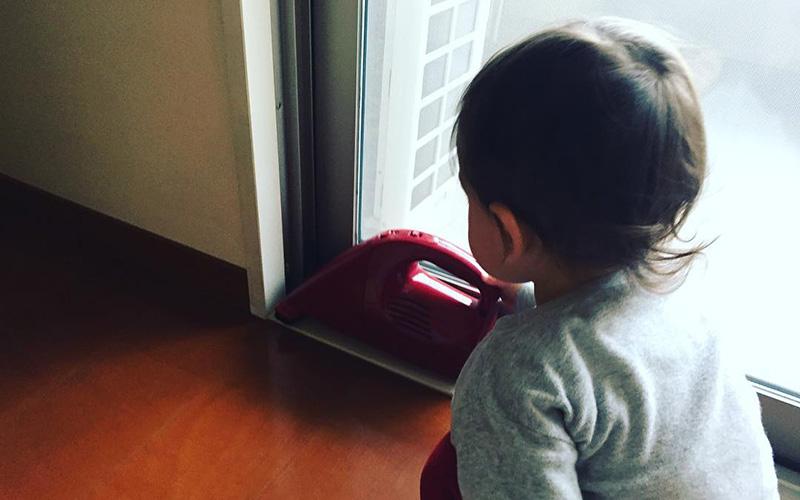 写真:じょーくんがハンディ掃除機で窓際を掃除している様子