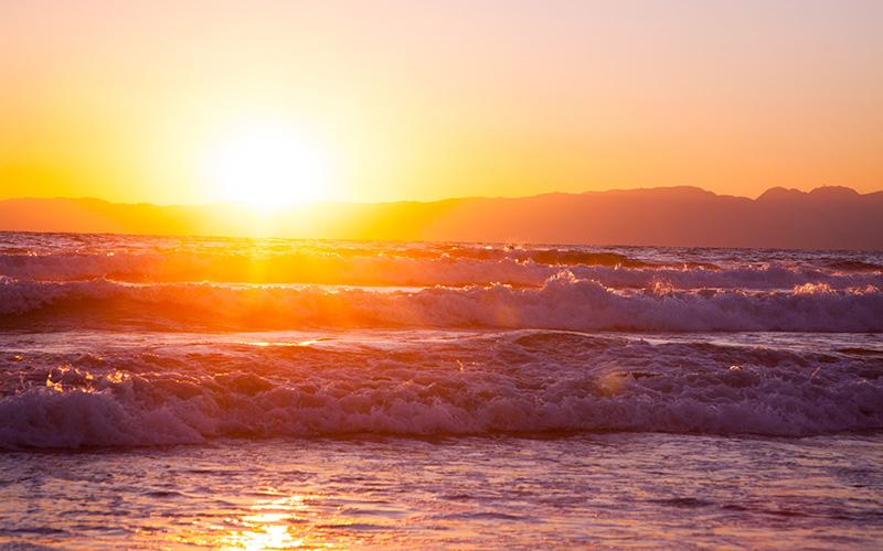 写真:日の出と荒波