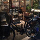写真:夜お店の前で自転車修理をする店主