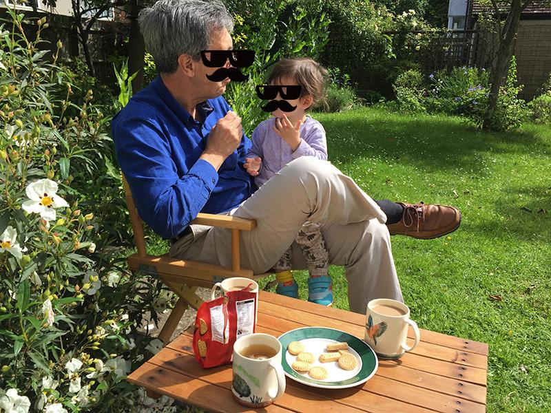 写真:庭でビスケットを頬張るじょーくんとイギリスのおじいちゃん